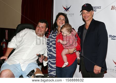 NEW YORK - MAY 21: Actor Gary Sinise (R) poses for pictures at a benefit concert at the Hard Rock Cafe on May 21, 2015 in New York City.