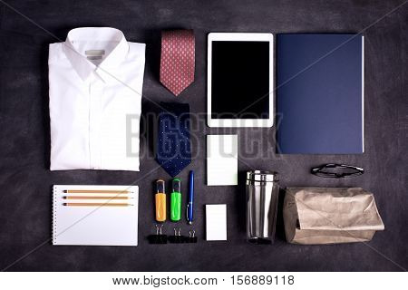 Business objects on the desk, including digital tablet, shirt, ties, lunch box, paper and pencils, top view, black chalkboard, toned image