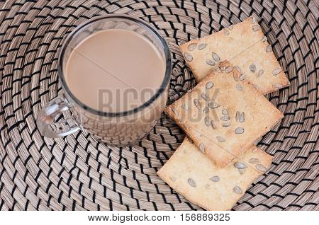 cup of hot cocoa and cookies with seeds and nuts on napkin plexus mat