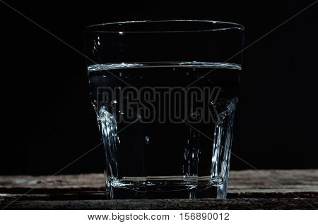 glass of clear water on wooden textural background