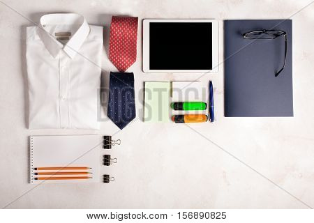 Business objects on the desk, including digital tablet, shirt, ties, lunch box, paper and pencils, copy space