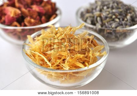 Dried marigold (calendula) petals with lavender and rose for beauty treatments in clear glass bowls - front view with copy space