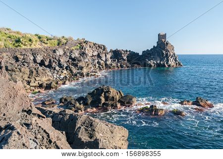 Rocky coastline of lava cliff near Acireale (Sicily) with a watchtower in the background