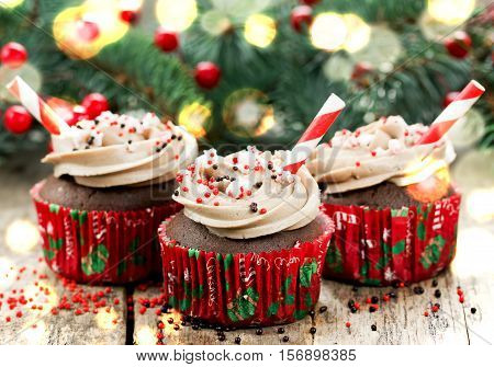 Christmas and New Year cupcakes - chocolate cakes with cream sprinkles and peppermint candy cane bites decorated for holiday dinner sweet treats for kids