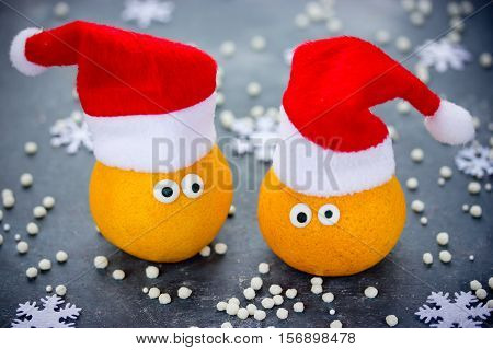Tangerine with eyes in Santa hat Christmas Xmas New Year concept fresh ripe and sweet mandarin orange clementine tangerine symbol winter holidays