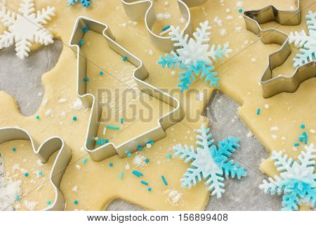 Christmas baking background: dough cookie cutters and snowflakes of confectionery sugar paste