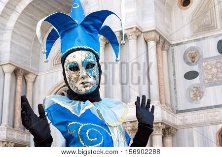 VENICE, ITALY - FEBRUARY 16, 2015: Joker masked model with San Marco church on the background