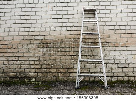 Metal ladder staircase on brick wall background