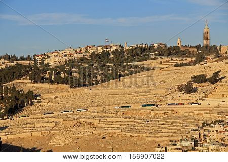 Cemetery and homes on the Mt. of Olives in Jerusalem, Israel.  Tour busses can be seen along the roadside.