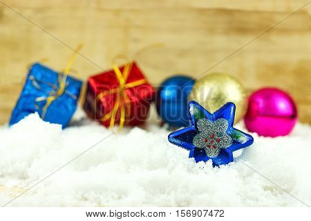Blue Star and Christmas decoration on white snow with wooden background