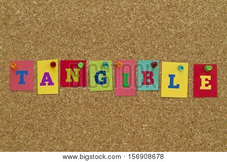 Tangible word written on colorful sticky notes pinned on cork board.