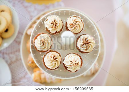 Close up, cupcakes with vanilla cream in white cakestand and jam cookies on plate. Studio shot.