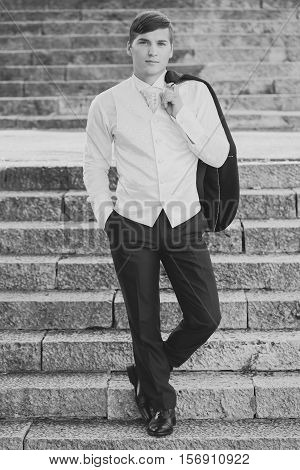 Young groom man with handsome face in wedding costume holding his suit on shoulder and another hand in pocket standing on stone upstairs outdoor black and white