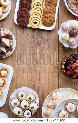 Naked cake with berries, cupcakes, chocolate chip cookies and spiral cookies, pie, tarts and cakepops laid on table. Studio shot on brown wooden background. Frame composition. Copy space. Flat lay.