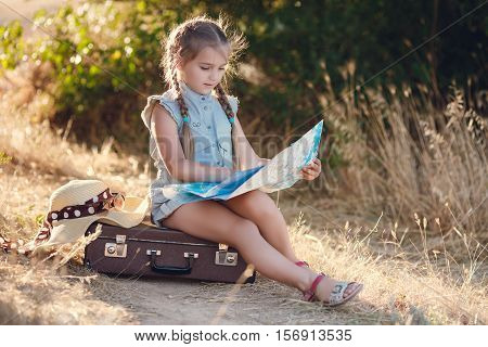 Young traveler girl-a brunette with braided pigtails,a light blue summer Romper,ears wearing earrings,a funny smile,resting sitting on an old brown suitcase on a country road near a green shrub,studying a map of the area