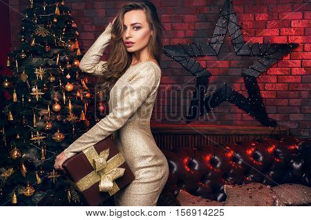 Happy New Year To You! Beautiful Girl With A Christmas Gift Stay In Front Of The Christmas Tree. Goo