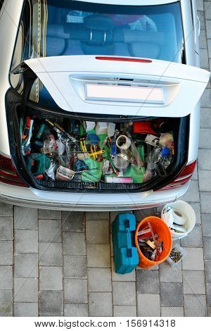 Open car trunk baggage compartment loaded with old work tools and junk on grey paving stone background