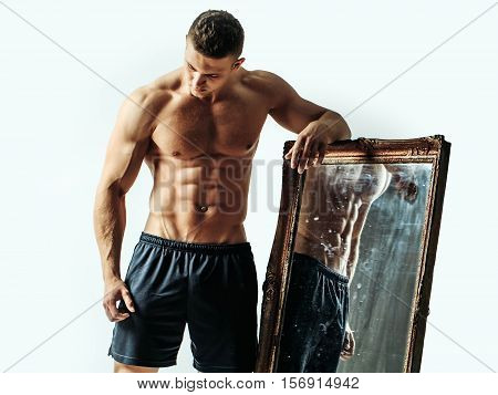 young handsome macho man with sexy muscular athletic body with bare torso and strong belly with six packs or abs in jeans holds big mirror isolated on white background