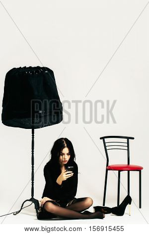 young sexy woman or girl in black stockings with long hair and pretty face near shoes chair and lamp holds mobile phone in studio isolated on white background copy space