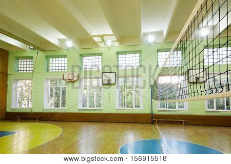 MOSCOW, RUSSIA - JUN 28, 2016: Gym with basketball hoops, volleyball net in 2107 school, In Moscow there are more than 1800 schools