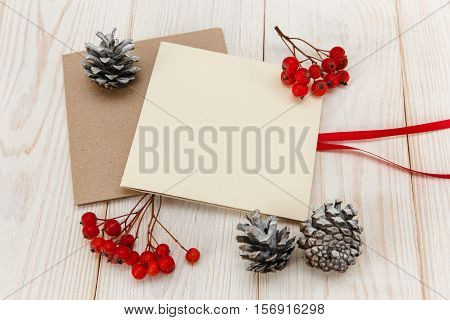 Christmas mokup.Empty cards with rowanberry and cones .White wooden table.Top view