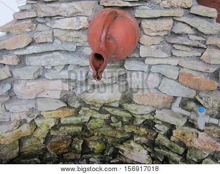 From the jug which is sticking out of a stone wall the stylized spring beats