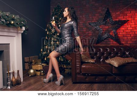 Girl In A Short Dress And Beautiful Shoes Sitting On A Leather Couch And Drinking Champagne After Th
