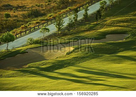 Sand bunker on the green golf course at sunrise