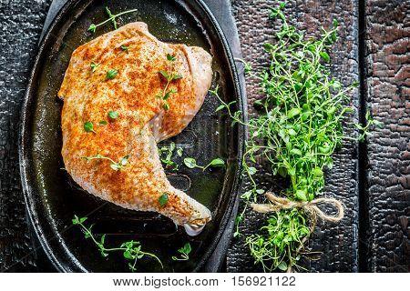 Chicken Leg With Fresh Marjoram On Black Burning Table