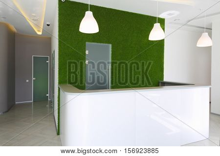 Empty reception room with desk, green lawn wall in business center