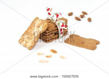 Closeup of a stack of spiced biscuits with almonds ( Spekulatius ) decorated with Christmas Bow surrounded by almonds and more biscuits on white background.