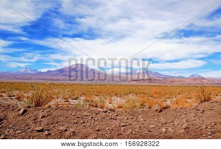 Panoramic view of the Atacama desert with a mountain range in the background and a blue sky with clouds close to San Pedro de Atacama in Chile South America
