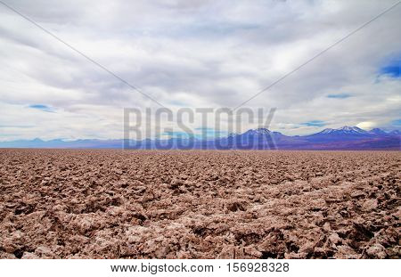 Panoramic view of salt flats in the Atacama desert with a mountain range in the background and a blue sky with clouds close to San Pedro de Atacama in Chile South America