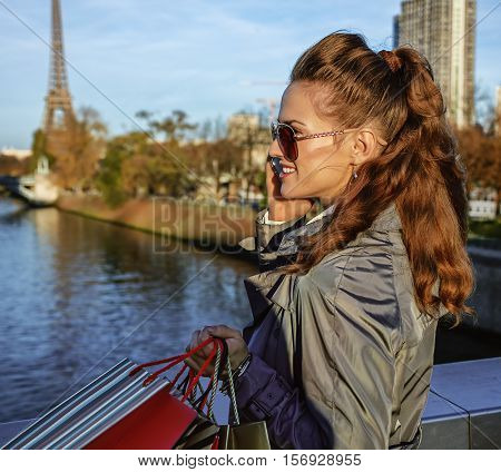 Young Fashion-monger Speaking On Smartphone Near Eiffel Tower