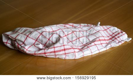 white red checkered wrinkled dishcloth on a wooden table