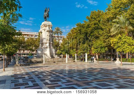 Overview of the New Square, Plaza Nueva, with the monument to King Ferdinand III in the center, in the sunny summer day, Seville, Andalusia, Spain
