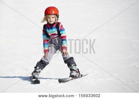 Happy child girl enjoying vacation in winter resort. Little girl skiing in mountains. Active sportive toddler wearing helmet learning to ski. Winter sport for family. Skier racing in snow.