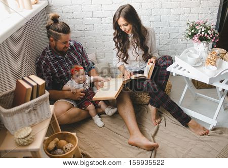 Parents with little baby reading story indoors
