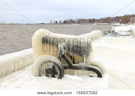 Old ice-covered cannon on a winter embankment, Petrozavodsk, Russia