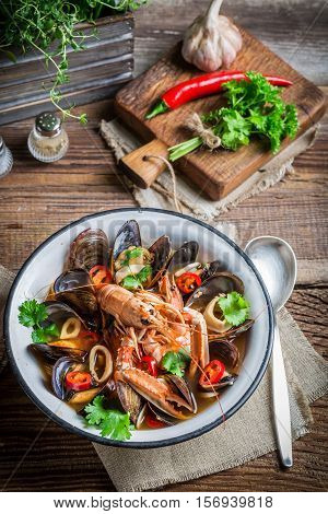 Seafood Soup With Mussels And Langoustines On Old Wooden Table