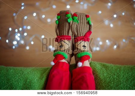 Legs in socks on a green couch. house. composition in red and green.