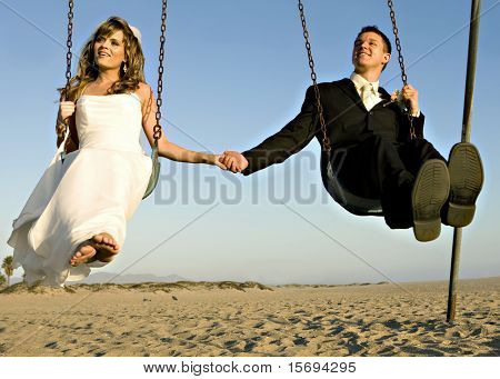 Young bride and groom playing on a swing set