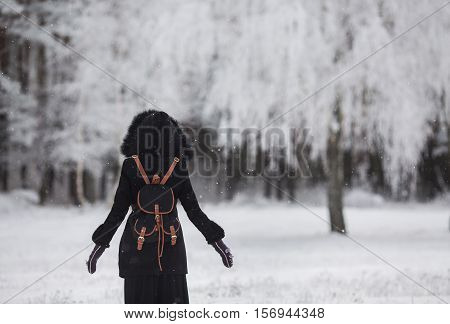 girl standing in front of a beautiful winter forest silhouetted against the winter forest a man standing on the snow