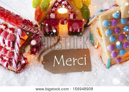 Label With French Text Merci Means Thank You. Colorful Gingerbread House On Snow And Snowflakes. Christmas Card For Seasons Greetings