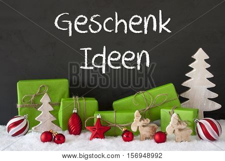 German Text Geschenk Ideen Means Gift Ideas. Green Gifts Or Presents With Christmas Decoration Like Tree, Moose Or Red Christmas Tree Ball. Black Cement Wall As Background With Snow.