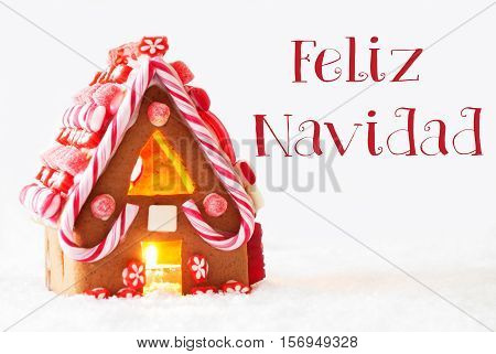 Gingerbread House In Snowy Scenery As Christmas Decoration With White Background. Candlelight For Romantic Atmosphere. Spanish Text Feliz Navidad Means Merry Christmas
