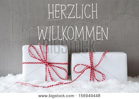 German Text Herzlich Willkommen Means Welcome. Two White Christmas Gifts Or Presents On Snow. Cement Wall As Background. Modern And Urban Style.