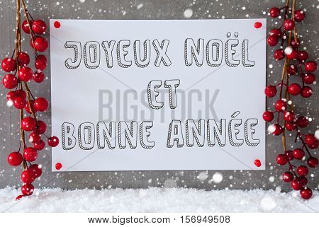 Label With French Text Joyeux Noel Et Bonne Annee Means Merry Christmas And Happy New Year. Red Christmas Decoration On Snow. Urban And Modern Cement Wall As Background With Snowflakes.