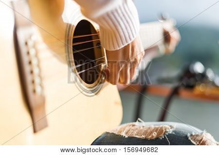 Music close-up. Musician with a wooden guitar