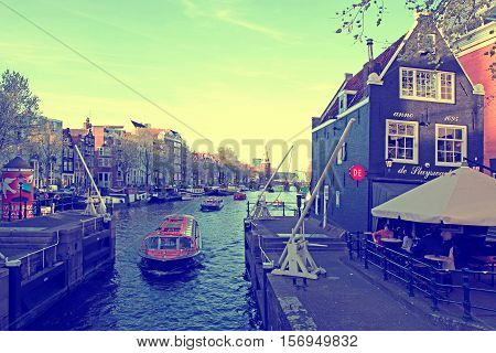 AMSTERDAM, NETHERLANDS - MAY 5, 2016: Cruising boat in Oide Schaans canal sluice and the old medieval Sluishuis restaurant in Amsterdam, Netherlands. This cafe is situated near to the Nieuwmarkt and is opposite the Rembrandt-house. Vintage toned image